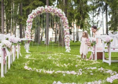 Wedding benches with guests and flower arch for ceremony outdoors